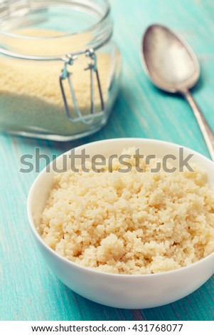 cooked couscous in a white bowl , couscous in a glass jar on a blue wooden background (Toning)