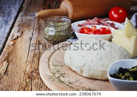 cooked dough and ingredients for pizza on the old wooden table. diet or cooking concept. copy space background - stock photo