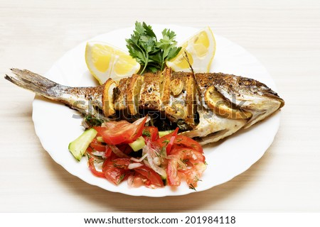 Cooked fish sea bream fish with lemon, parsley,garlic. - stock photo