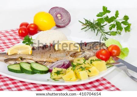 Cooked fish with vegetables, herbs and lemon on the plate - stock photo