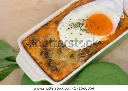 Cooked green lentils (Lens culinaris) mixed with eggs, cheese and spices and baked in an owen, served with sunny side up fried egg - stock photo