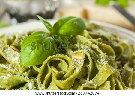 Cooked homemade spinach pasta with pesto, pine nuts, Parmesan cheese and basil leaves  - stock photo