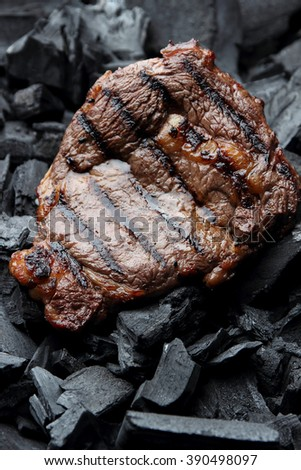 Cooked juicy steak on the coals.
