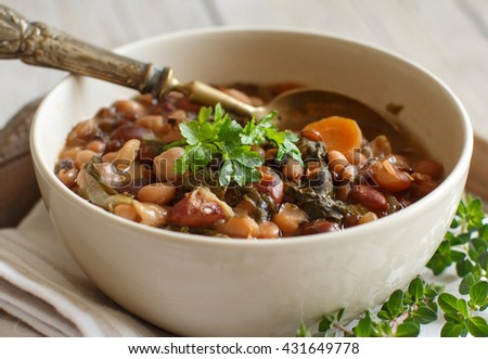 Cooked legumes and vegetables in a bowl on the old wooden table