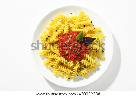 Cooked macaroni, served with sauce on white plate against a white background. Close up, top view, high resolution product. - stock photo