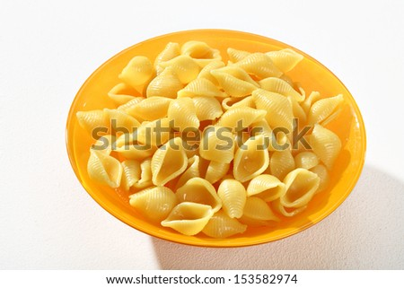 Cooked macaroni shells / a portion of cooked macaroni, served without sauce on an orange plate against a white backdrop  - stock photo