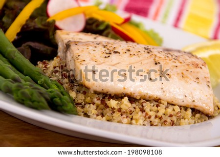 cooked mahi mahi fish fillet dish on quinoa with vegetables  - stock photo