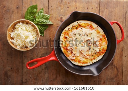 Cooked mozzarella and ham pizza on a skillet overlook shot - stock photo