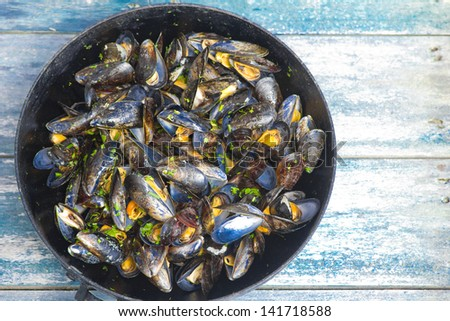 Cooked mussel with olive oil and herbs on fry pan. Very shallow depth of field. - stock photo