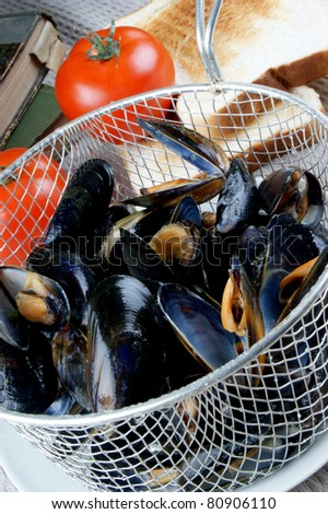 cooked mussels in a colander with tomato