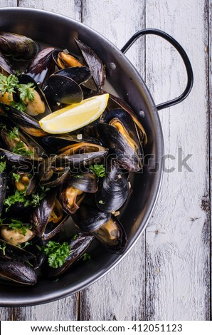 Cooked mussels in a pan on white wooden background