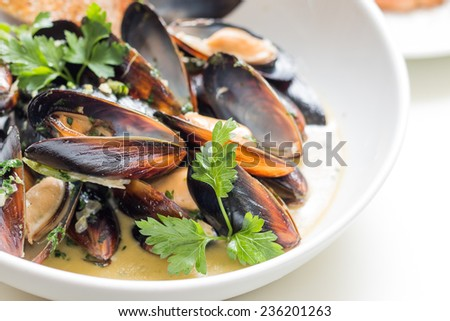 Cooked mussels in a with bowl with french toast