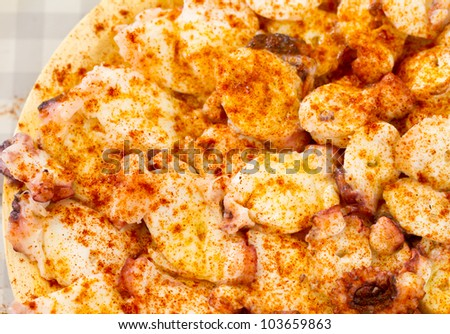 cooked octopus slices dressed with paprika over wooden plate, top view