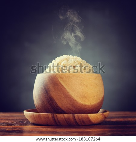 Cooked organic basmati brown rice in wooden bowl with hot steam smoke on dining table. Low light setting with retro revival style. - stock photo