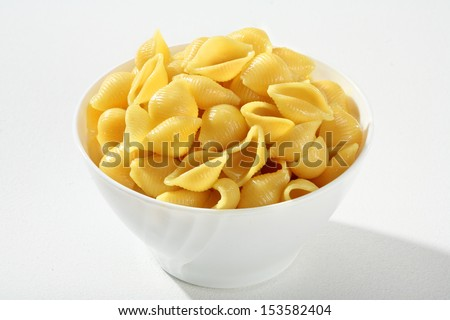 Cooked pasta shells / a portion of cooked pasta, served without sauce on a white ceramic bowl against a white backdrop  - stock photo