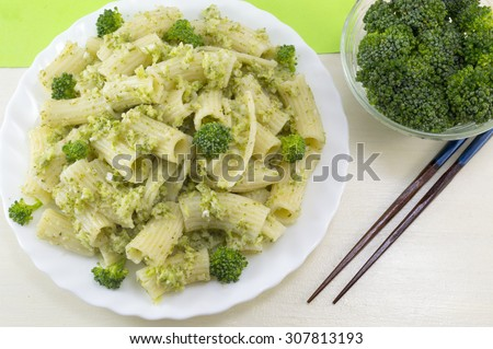 Cooked pasta with broccoli served with cooked broccoli in a white bow on a wooden table. Eating with chopsticks