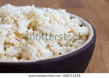 Cooked quinoa in a ceramic bowl on wood table. - stock photo