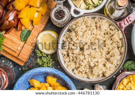Cooked quinoa in pot with fresh fruits and vegetables ingredients for tasty cooking , preparation on rustic kitchen table, top view, close up. Vegan Superfood, healthy eating or diet concept. - stock photo