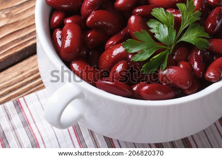 cooked red kidney beans in white bowl close-up on a wooden table. horizontal top view  - stock photo