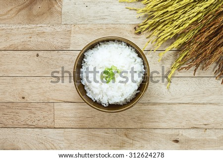 Cooked rice and paddy rice on wood table at top view - stock photo