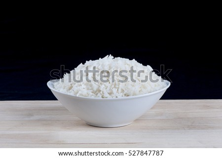 Cooked rice in bowl on the table with dark background.