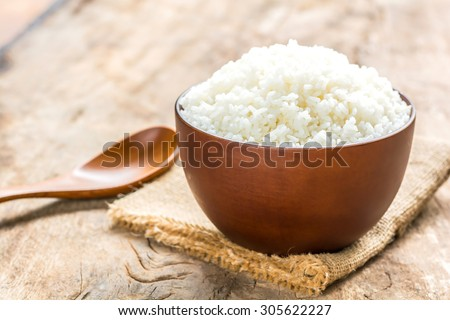 Cooked rice in bowl with spoon on old wooden table