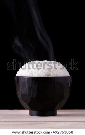 Cooked rice in japanese bowl on black background with smoke, steamed rice