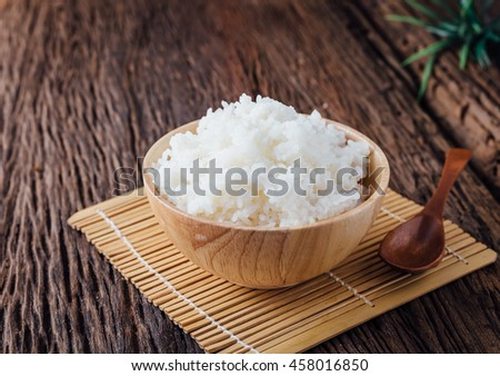 cooked rice in wooden bowl on wooden background,hot cooked rice in bowl