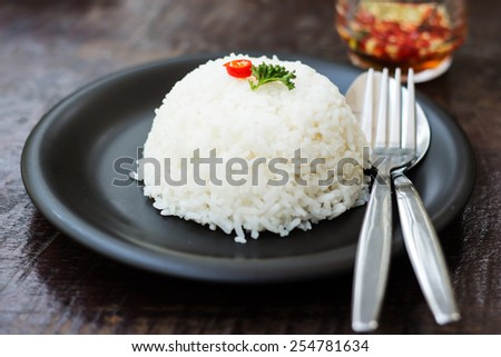 cooked rice with a spoon and fork on dish - stock photo