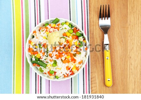 Cooked rice with vegetables on wooden table  - stock photo