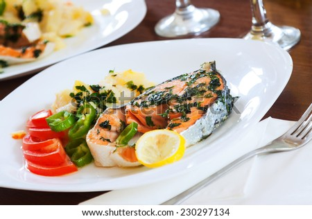 Cooked salmon fish on plate at table - stock photo