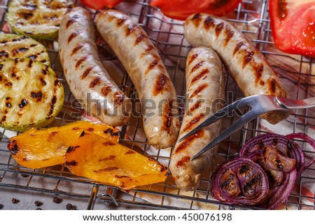 Cooked sausages with vegetables and spices on the grill grate. - stock photo