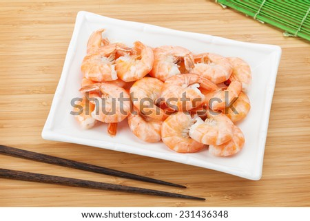 Cooked shrimps and chopsticks. View from above on wooden table - stock photo