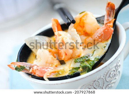Cooked shrimps on a decorative spoon with fresh herbs - stock photo