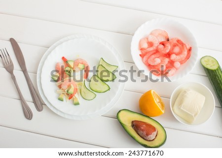 Cooked shrimps with avocado and mozzarella on white wooden table - stock photo