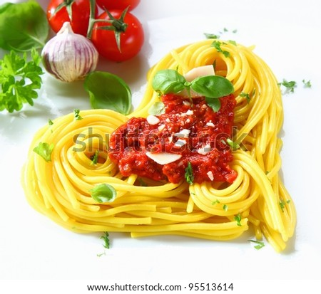Cooked spaghetti arranged in a heart shape topped with tomato sauce and fresh basil - stock photo
