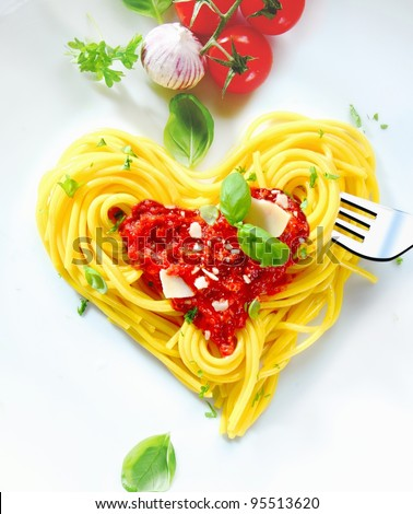 Cooked spaghetti carefully arranged in a heart shape and topped with tomato sauce accompanied by raw ingredients to the side - stock photo