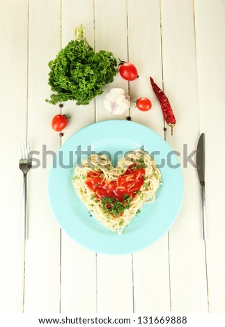 Cooked spaghetti carefully arranged in  heart shape and topped with tomato sauce, on  wooden background - stock photo
