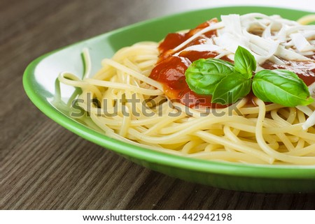 Cooked spaghetti with traditional italian tomato sauce served in a green plate on a wooden table - stock photo