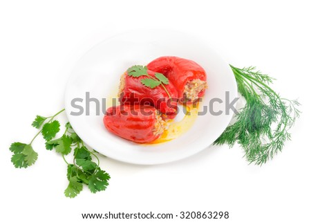 Cooked stuffed bell peppers on a white dish and a sprigs of cilantro and dill on a white background. Isolation.