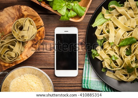 Cooked tagliatelle pasta ingredients and a smartphone - stock photo