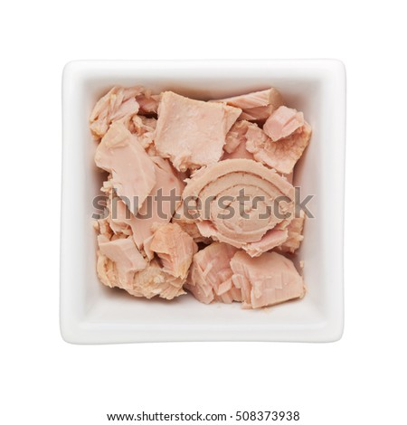Cooked tuna chunks in a square bowl isolated on white background