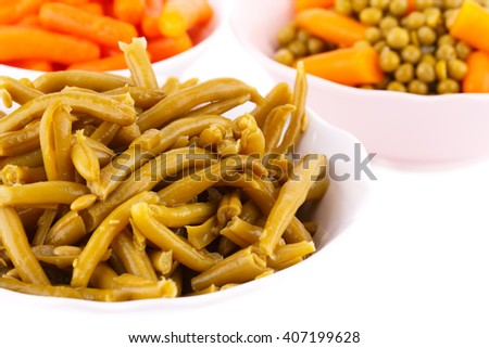 Cooked vegetables in bowls on white background. - stock photo