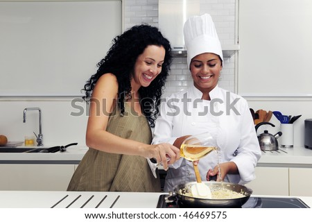Cookery course: pouring wine into a pan with risotto - stock photo