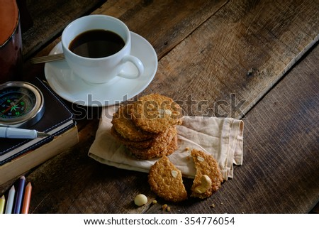 Cookie and cup of  coffee on wooden table  vintage color.