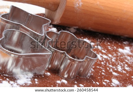 Cookie cutters and rolling pin lying on dough for cookies, concept for baking - stock photo