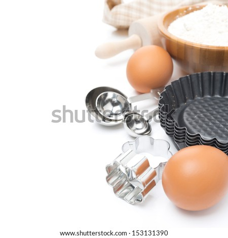 cookie cutters, measuring spoons, eggs and flour for baking isolated on white - stock photo