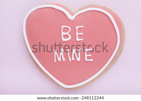 Cookie, Heart shaped biscuit with pink and white frosting on pink background - stock photo