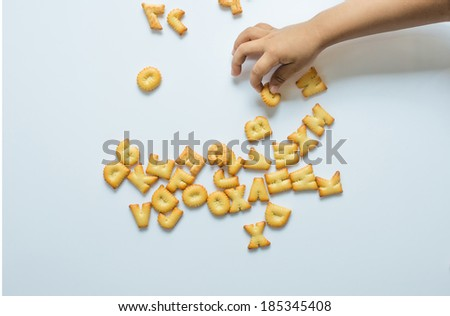 Cookies ABC in child's hand isolated on white background - stock photo