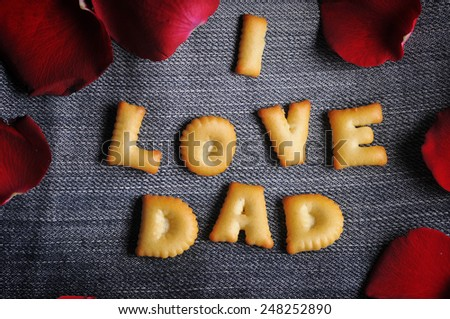 Cookies ABC in the form of word I LOVE DAD alphabet with red rose petal on old jean background, Valentines day - stock photo